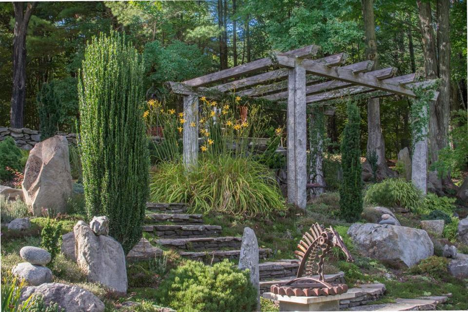 Stone steps lead to a pergola that provides a view of the entire garden.