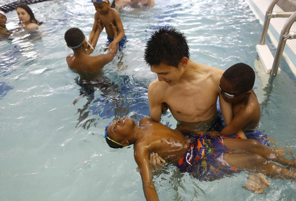 Swim instructor Tommy Drews, 17, guides Isaiah Peters in a floating drill, with Joel Cabral keeping close watch, at a Water Warriors class.