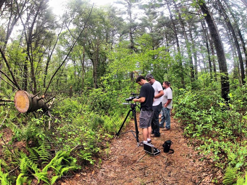Codirectors Aaron Cadieux (left) and Manny Famolare confer on a scene being shot in a swamp in Raynham for their documentary film.