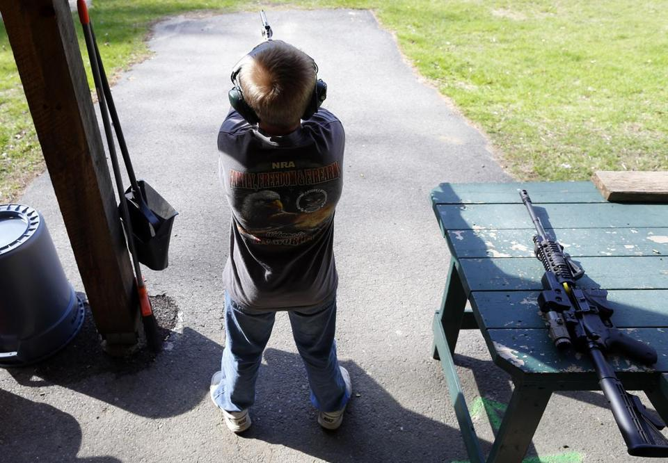 Rio Ferguson, 10, shoots a Smith and Wesson 626 .22-caliber revolver at a target at Marlborough Fish and Gun Club.