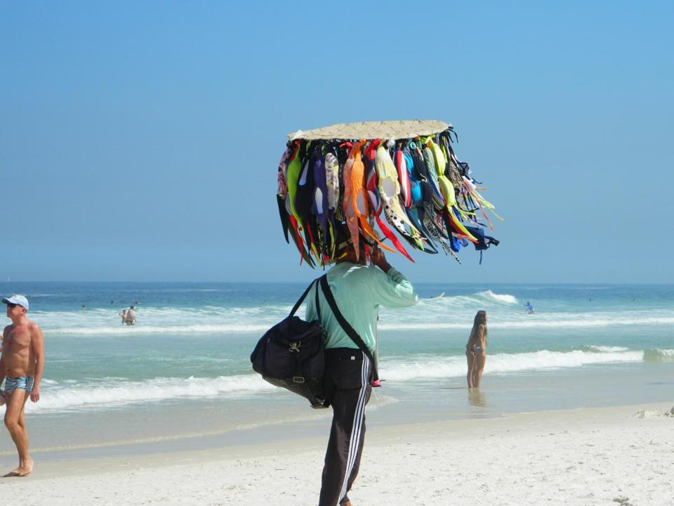 A vendor displays his bikinis (sold by the piece) on an umbrella-like contraption at Rio de Janeiro's Barra da Tijuca beach.