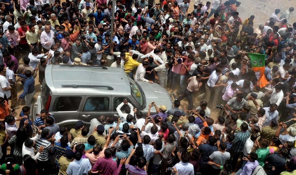 Bystanders and the media surrounded the vehicle of Narendra Modi as he left his mother's home in Gandhinagar, India.