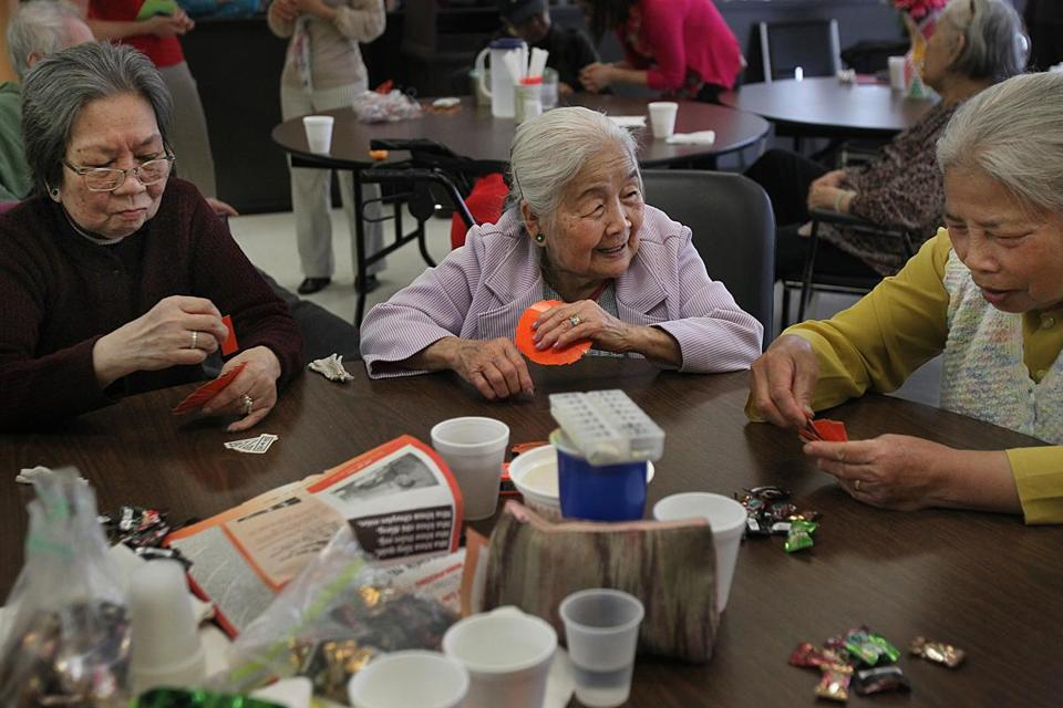 From left, Thien Luu, Bay Nguyen, and Duyen Tran engage in a friendly card game at Dorchester's Kit Clark Senior Center.
