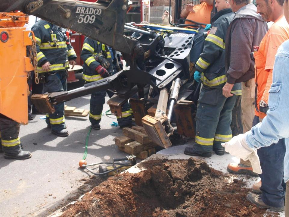 A Department of Public Works employee's legs became wedged between the controllers of his loader and a dump truck.
