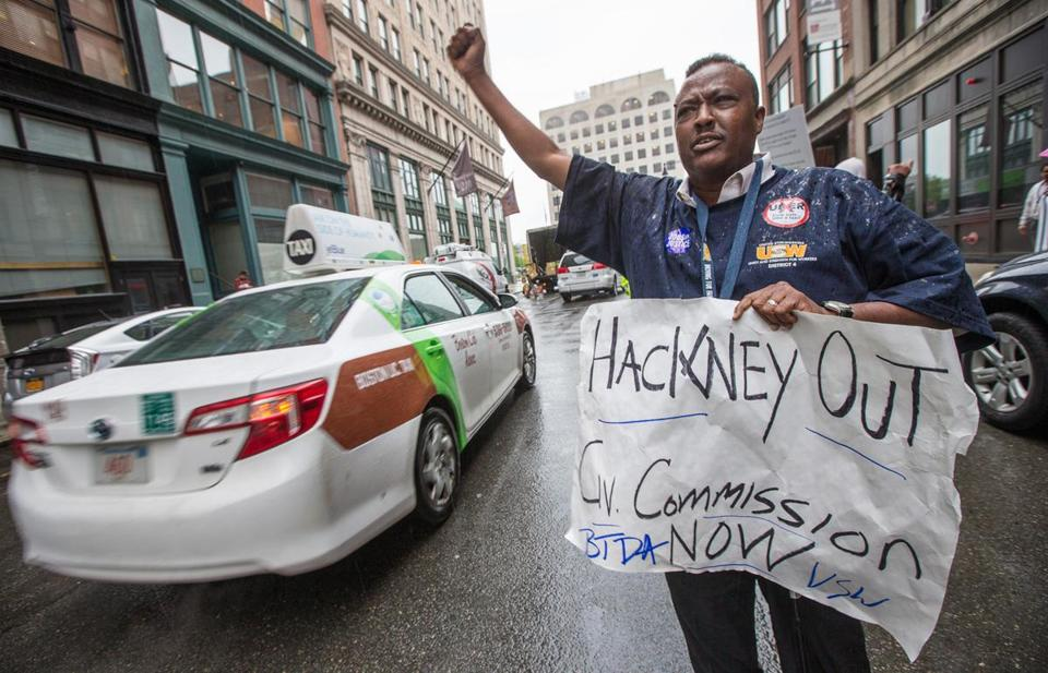 Taxi driver Ahmed Farah protests in front of the Uber office in Boston last month.