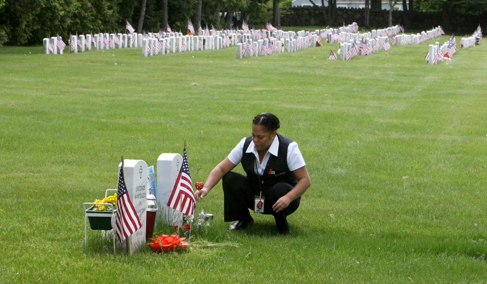 Yessenia Reynoso placed flowers at the grave of her brother, Denis Reynoso,  in the section of Pine Grove Cemetery for Iraq war veterans in Lynn on May 24.