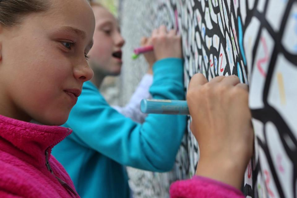 Sisters Kyla (left), 10, and Jada Ormsbee, 11, of Sterling, were two of the first people to work on the mural outside the Prudential Center.