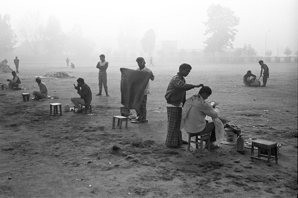 "From top: ""Barbers await clients in the early morning winter fog,"" ""Monks and pilgrims on the Boudhanath Stupa, Kathmandu,"" and ""A Newar Father and son manufacture bricks from wet clay."""
