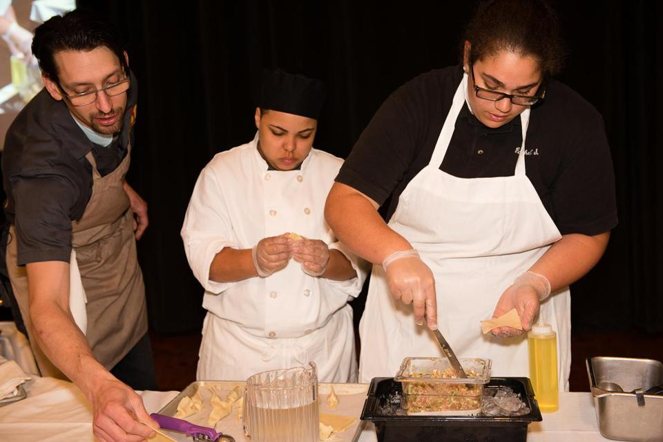 Culinary arts students Melinda James (center) and Rachel Silva helped chef Abraham Conlon make potstickers.