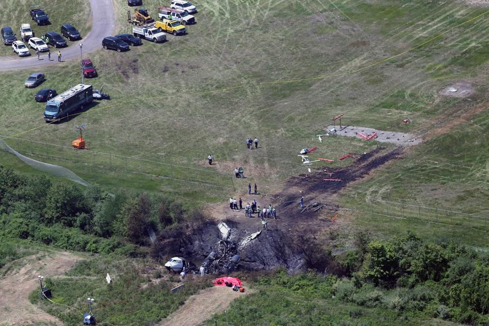 More than a dozen National Transportation Safety Board investigators scoured the crash site at Hanscom Field in Bedford on Monday.