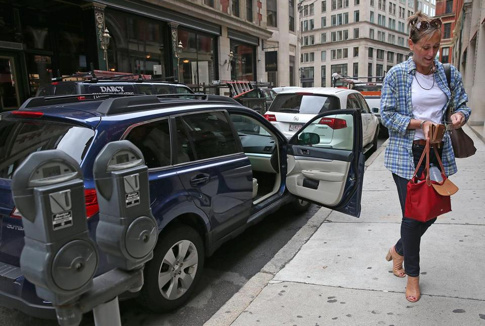 Amy Coon of Duxbury searched her purse for quarters to pay for a metered parking space in Boston. A proposed smartphone app would change the way drivers pay for street spots.