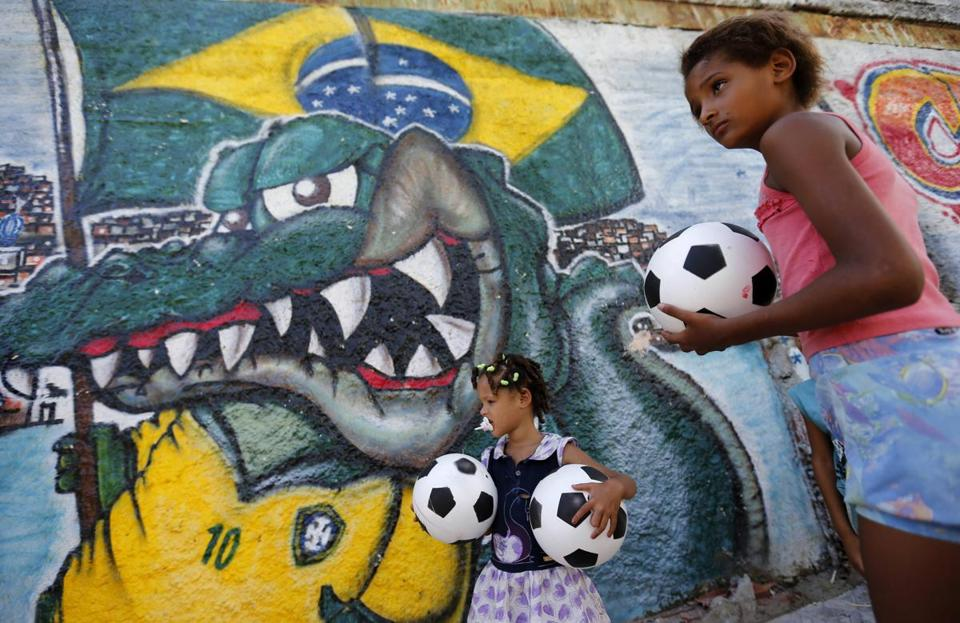Children stand in front of a graffiti-covered wall at the Jacarezinho slum in Rio de Janeiro. The photo was taken during a protest against conditions in Rio' slums. Participants called on the Brazilian government to bring education, health and public services up to the same standards as the 2014 World Cup stadiums.