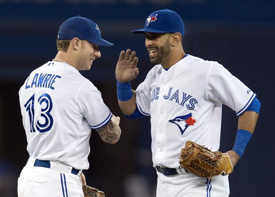 Jose Bautista and Brett Lawrie celebrated after defeating the Cardinals in Toronto Friday.