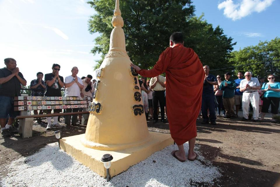 A Cambodian Buddhist monk prayed on Sunday at a stupa  in the new healing garden at Clemente Park in Lowell.