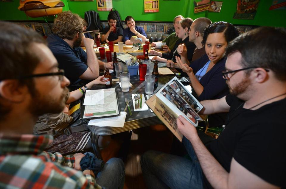 Nick Hansen of Natick, left, Cristina Rivera (cq) of Chelsea, second from right, and Jesse Bromley, of Dorchester were among during a comic book reading group meeting at the Friendly Toast in Cambridge. Josh Reynolds for The Boston Globe (Arts, Steinberg, lamy)