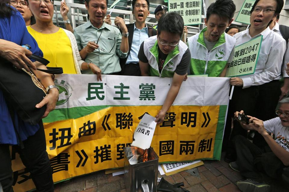 "Protesters in Hong Kong burned a mock ""white paper"" Wednesday that was released by the Beijing State Council saying it holds ultimate control over the former British colony."