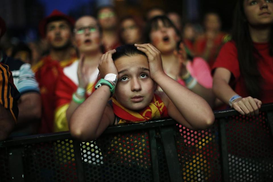 A Spanish soccer fan watching the game from Madrid can't hide her disappointment. AP Photo/Andres Kudacki