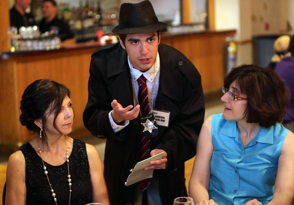 Actor Nataniel Cowper, as Detective Peter Ness, confers questioned diners about his case at the Murder Mystery Co. show at the Sons of Italy in Quincy.