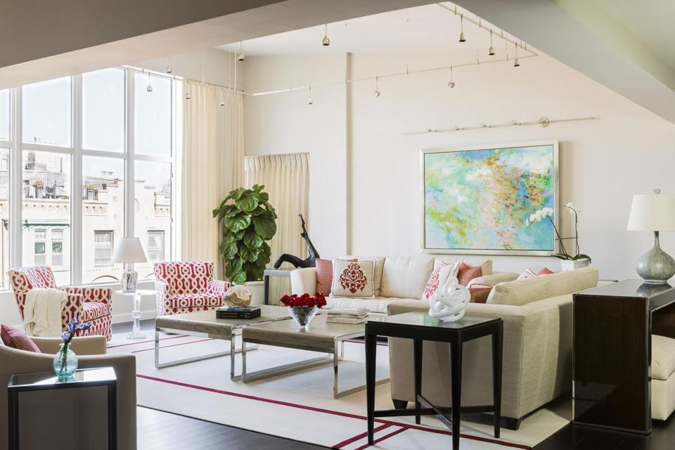 The living room (pictured) carries the palette of neutral colors with a splash of red that echoes the redesigned kitchen .