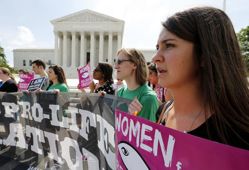 Anti-abortion protestors sing as they await the U.S. Supreme Court's ruling on a Massachusetts law that mandated a protective buffer zone around abortion clinics, outside the Court in Washington June 26, 2014. On a 9-0 vote, the court said the 2007 law violated the freedom of speech rightsof anti-abortion protesters under the First Amendment of the U.S. Constitution in preventing them from standing on the sidewalk and speaking to people entering the clinics. REUTERS/Jim Bourg (UNITED STATES - Tags: POLITICS CRIME LAW HEALTH CIVIL UNREST)