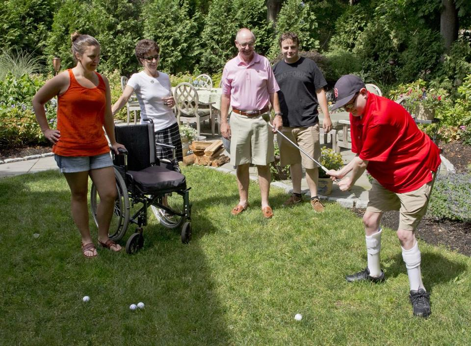 Milton, MA 6/29/2014 Philip Lussier (cq) hitting a chip shot in front of his parents Betsy and Phil Lussier (cq) and sister Amy Lussier (cq) and brother Mark Lussier in their backyard on Sunday June 29, 2014. (Matthew J. Lee/Globe staff) Topic: 02undiagnosed Reporter: Carolyn Johnson