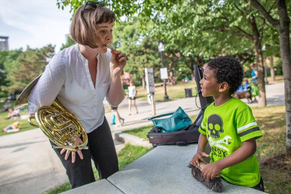 Rachel Childers, a French horn player with the Pops, showed Messiah, 4, how the mouthpiece works at Titus Sparrow Park in Boston.