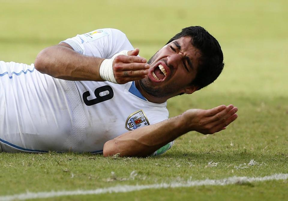 Uruguay's Luis Suarez was banned for four months by FIFA for biting the shoulder of Italy's Giorgio Chiellini during the group stage.  REUTERS/Tony Gentile/file