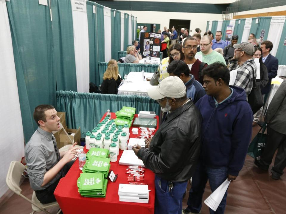 Bryan Preston of Hannaford supermarkets, left, talks with job seekers during a job fair at a community college in Hudson, N.Y.