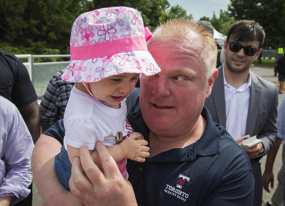 Toronto Mayor Rob Ford held a baby as he attended a publoc event on his first day back in public since returning from a rehab clinic for substance abuse problems.