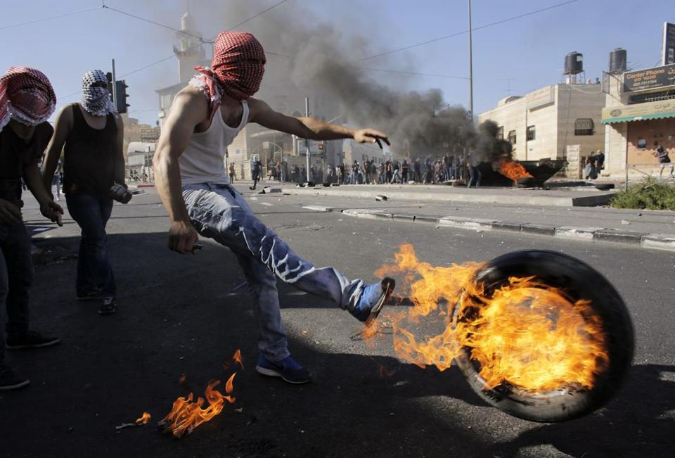 A Palestinian kicked a tire after setting it ablaze during clashes with Israeli police in a Jerusalem suburb on Wednesday.