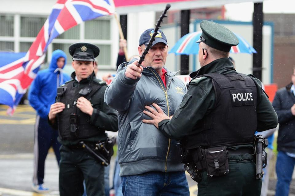 A policeman spoke to a loyalist outside the police station where Sinn Féin's Gerry Adams was being questioned May 4, 2014, in Antrim, Northern Ireland.