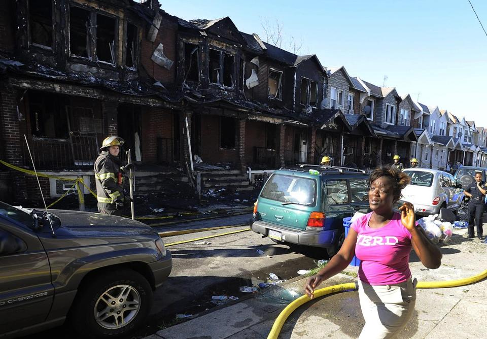 A woman wept in front of firefighters and burned row houses in Philadelphia. At least eight row houses were destroyed.