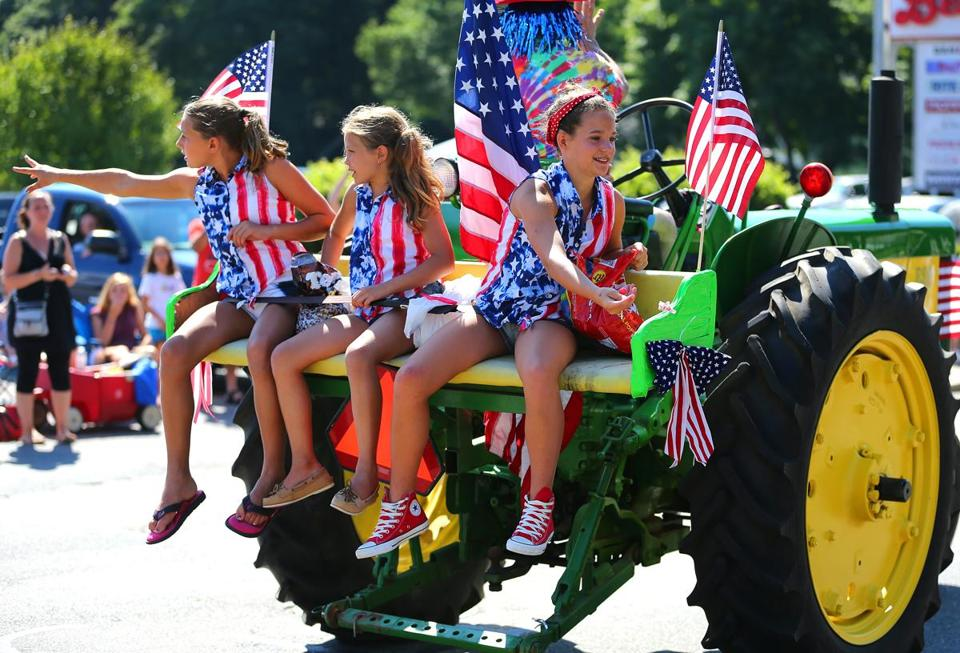 Girls in flag-themed attire sitting on the back of a tractor threw candy to the hundreds of spectators flanking the parade route.