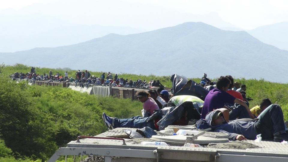 People hoping to reach the US rode atop a freight train in the Mexican state of Oaxaca.