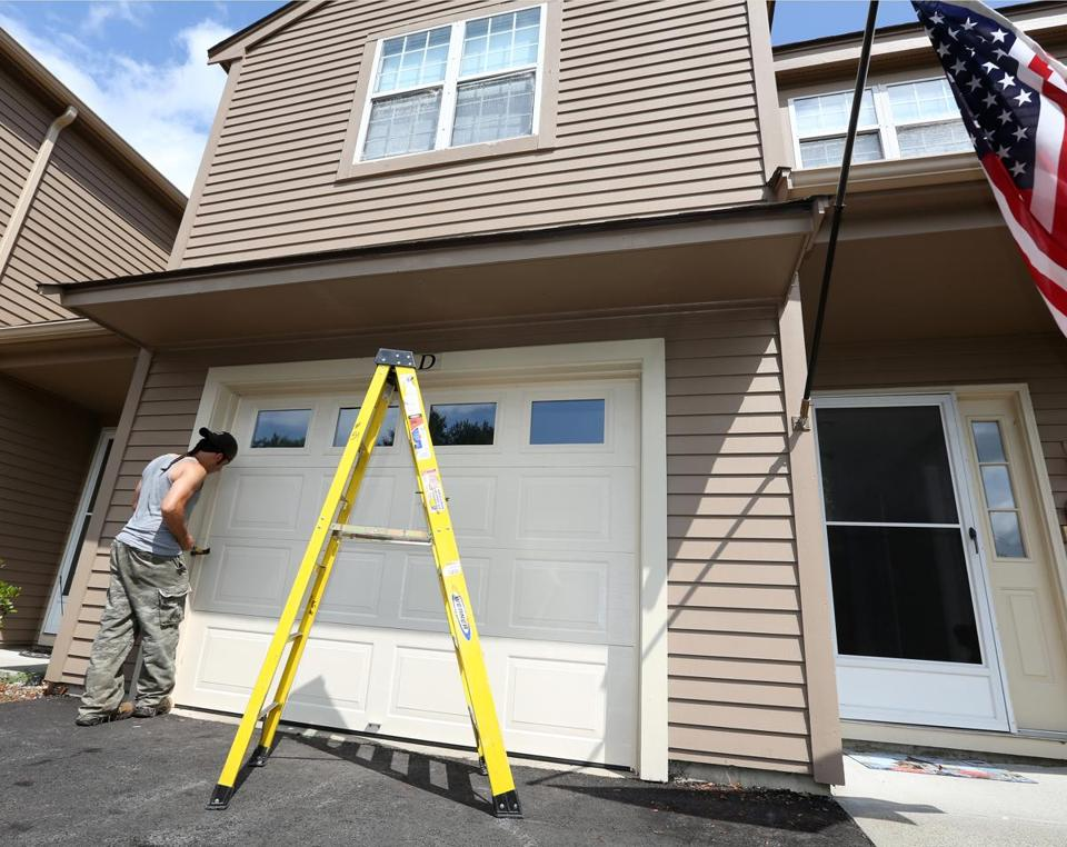 Jim and Teresa Anapol left a four-bedroom house in Stow for the convenience of a condo, here getting a new garage door.
