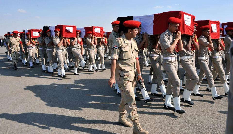 Egyptian soldiers, carrying coffins of troops killed in Farafra, marched at a funeral at Almaza military airport.