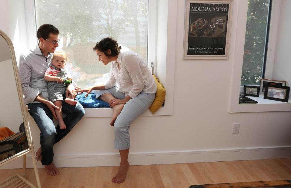 Maria Cramer at home with her husband, Michael Levenson, and their toddler son.