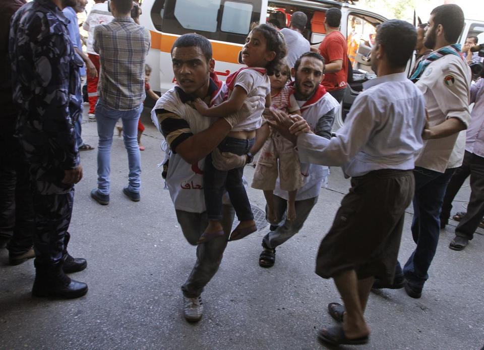 Palestinian medics carried children wounded in the strike on a compound housing a UN school in Gaza on Thursday.