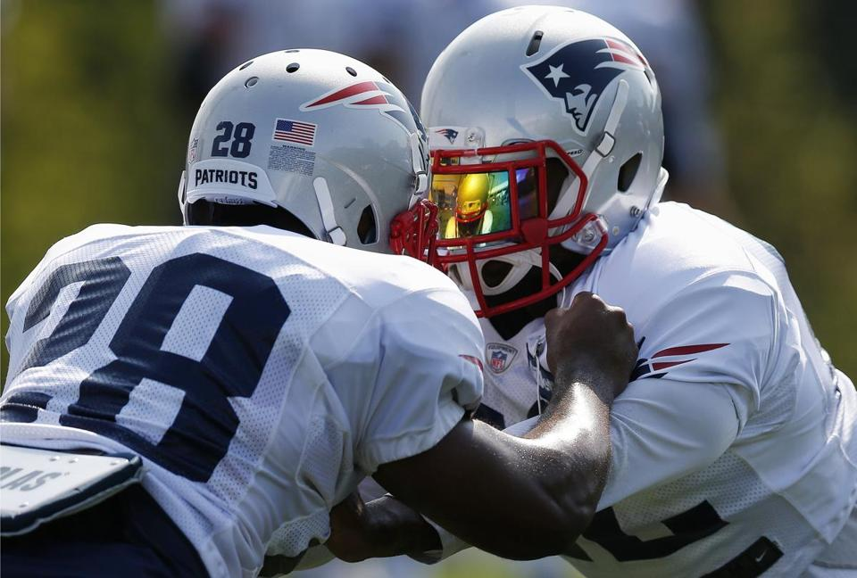 Patriots running backs James White (28) and running back Stevan Ridley (right) run a drill Saturday.