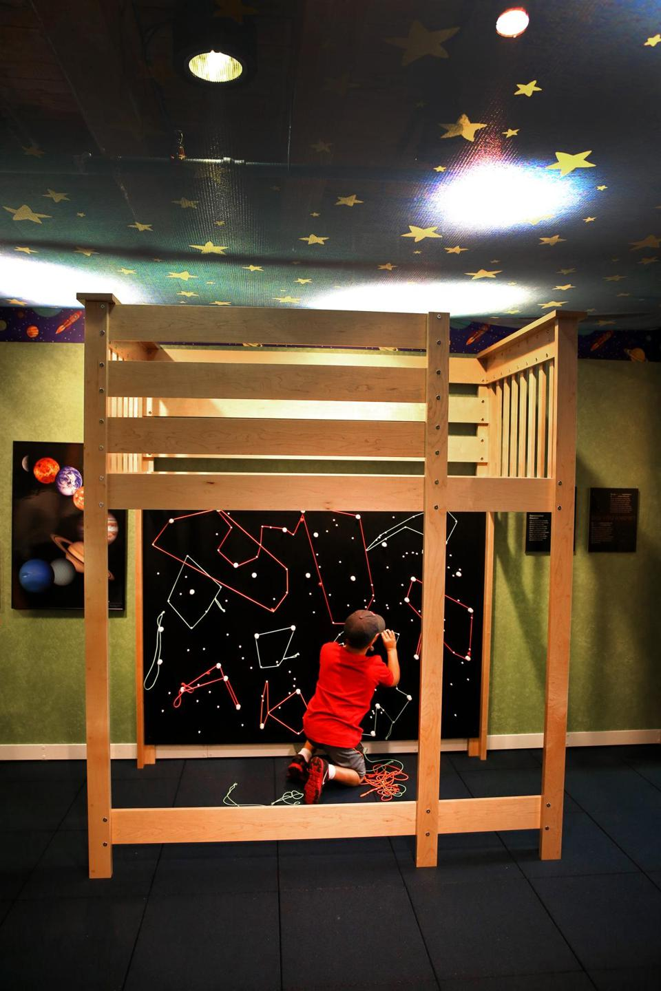 "Ryan Sevigny, 8, diagramming some constellations in a children's bedroom that is part of the ""My Sky"" exhibit."