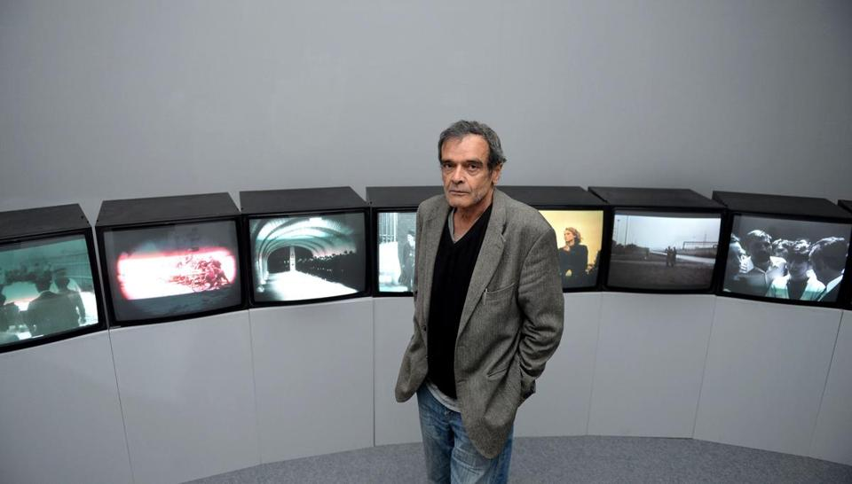 "Mr. Farocki with his 12-screen installation, ""Workers Leaving the Factory in Eleven Decades."""