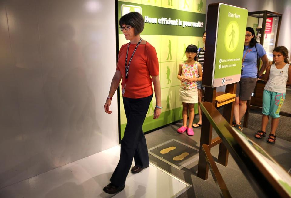 Jennifer Sullivan, who has lost more than 70 pounds, tries out an interactive walking display at the Museum of Science.