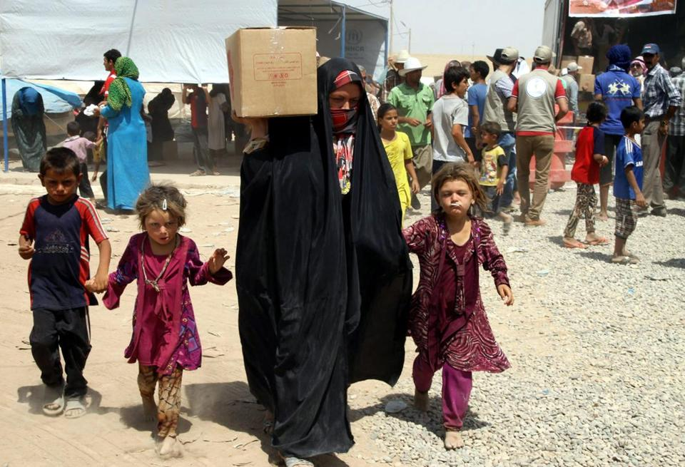 Iraqi refugees receive humanitarian aid at a camp near Irbil.