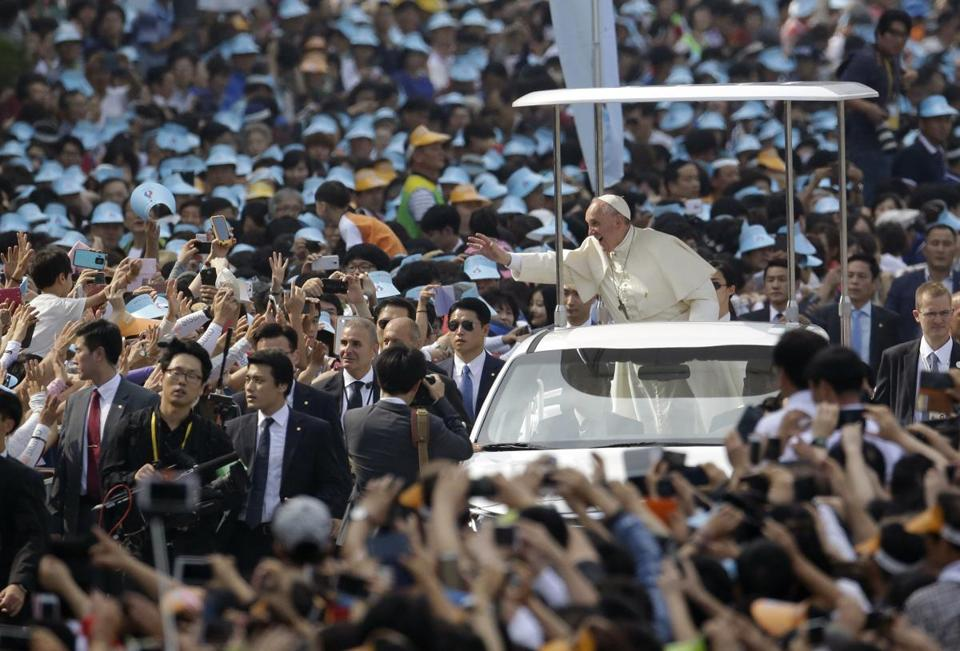 Pope Francis was greeted by the faithful as he arrived for a beatification Mass on Saturday in Seoul.