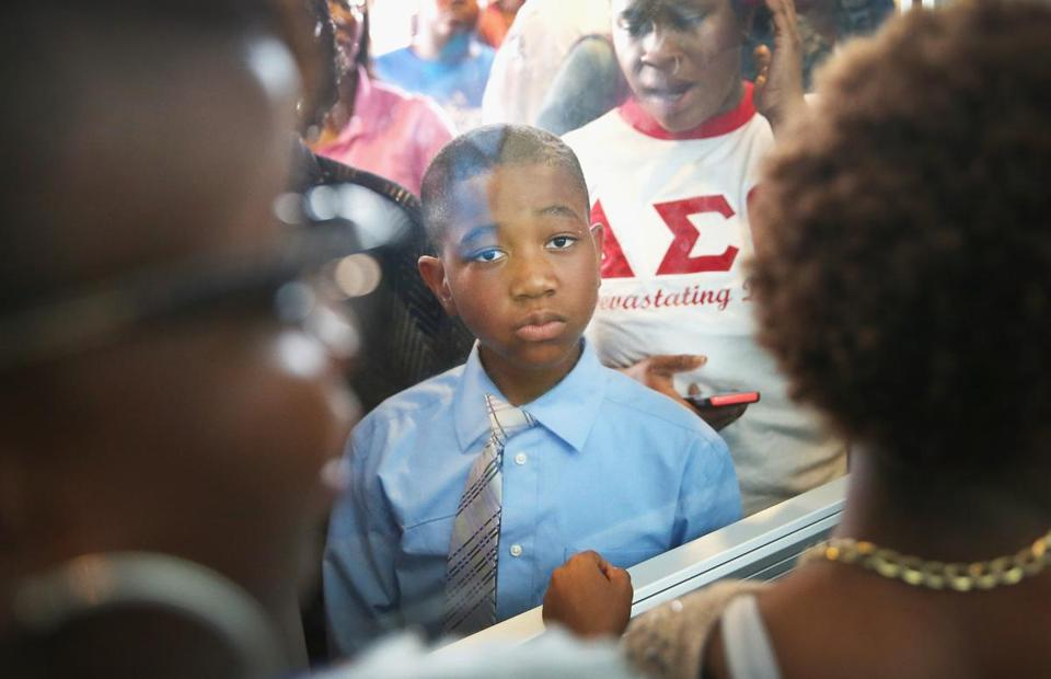 An overflow crowd watched from outside the door of Greater Grace Church during a rally in Ferguson, Mo., Sunday.