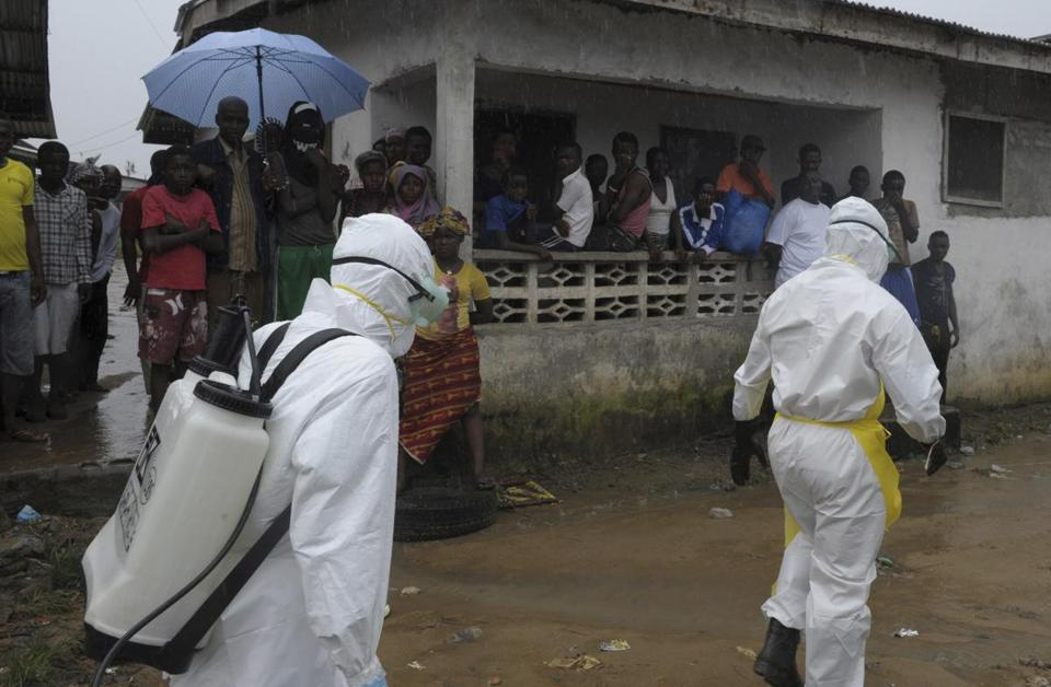 Health workers in protective clothing prepared to remove an abandoned body with Ebola symptoms from the Duwala market in Monrovia on Sunday.