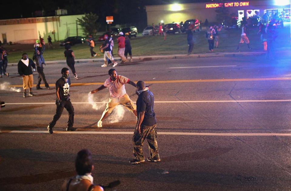 A demonstrator protesting the killing of teenager Michael Brown by a Ferguson police officer threw a tear gas grenade back toward police on Sunday.
