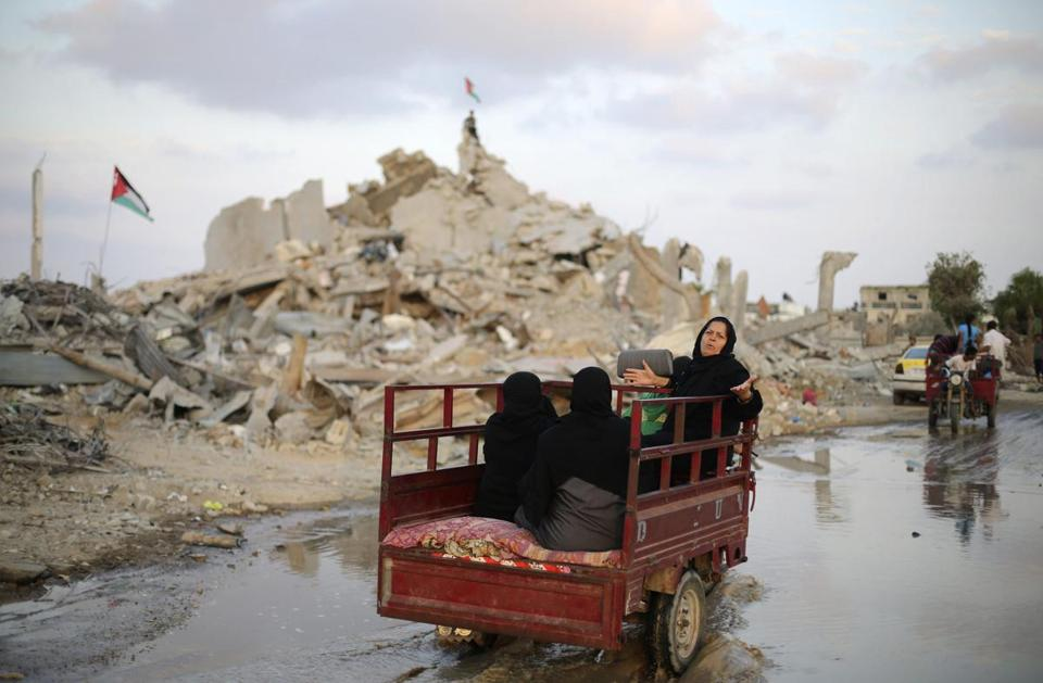 Palestinians rode in a motorized rickshaw past the ruins of a house in the southern Gaza Strip on Monday.