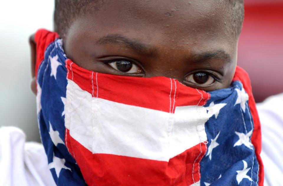 A young protester covers his face with the US flag in Ferguson Monday.
