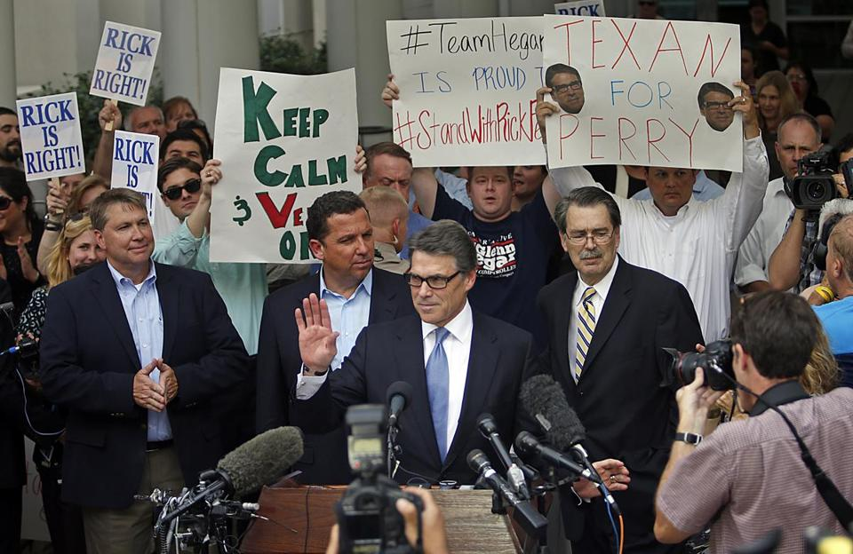 Texas Governor Rick Perry acknowledged supporters after he was fingerprinted in Texas Tuesday. Perry stood by his veto of funds for a Texas public corruption unit.